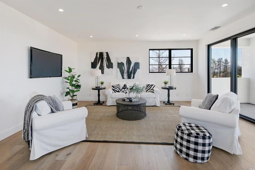 White modern living room with black accents and black windows