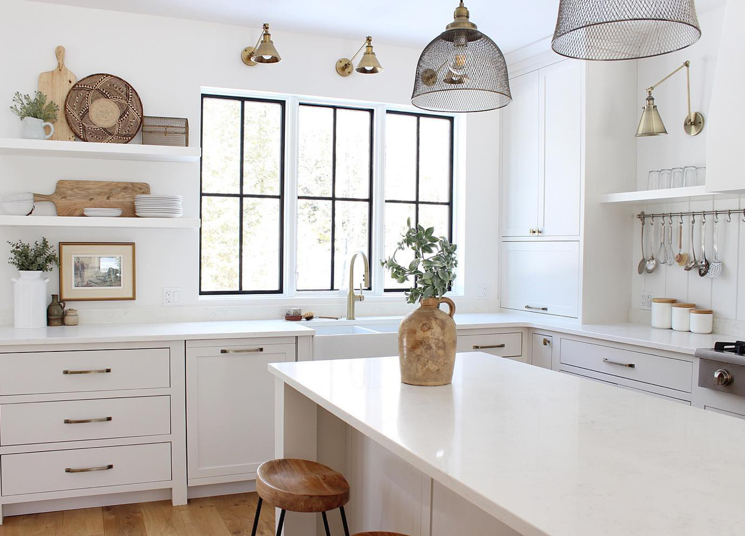 Black grille windows in white kitchen with wood accent pieces