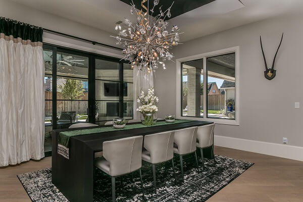 Modern dining room feature white casement windows, green table, and spiral metal chandelier
