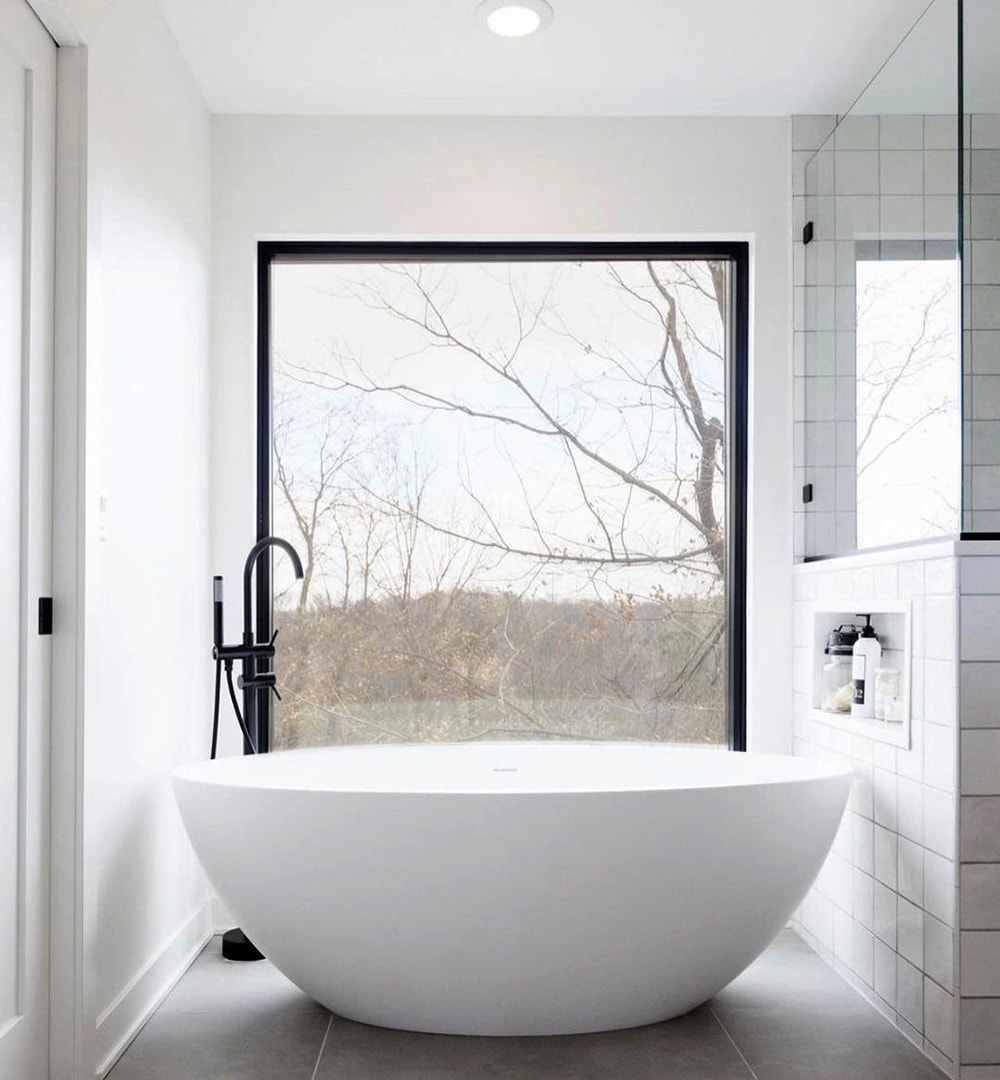 White bathroom features black rectangular window without grilles to  light bathtub area.