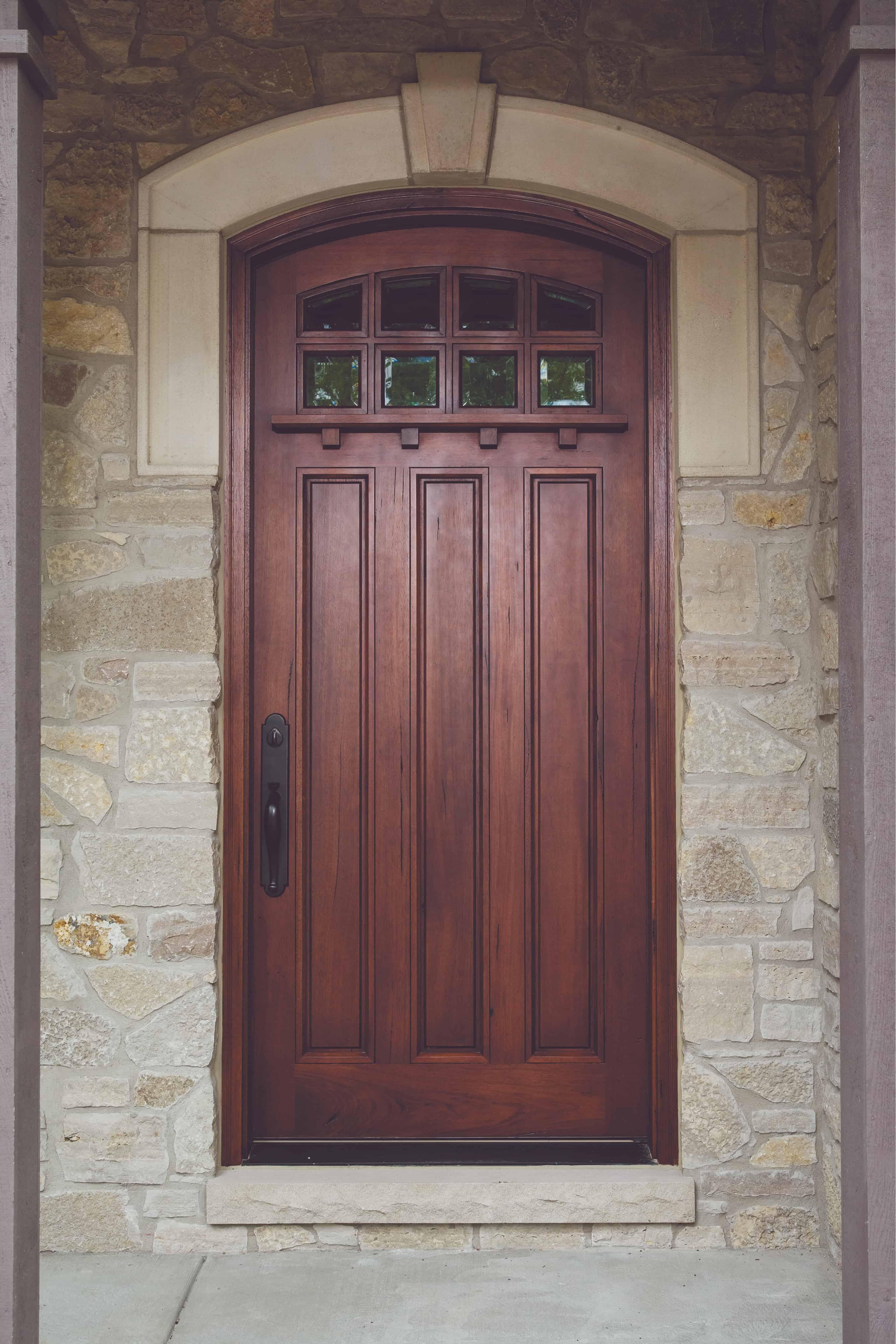 Craftsman style mahogany wood door set in stone entryway