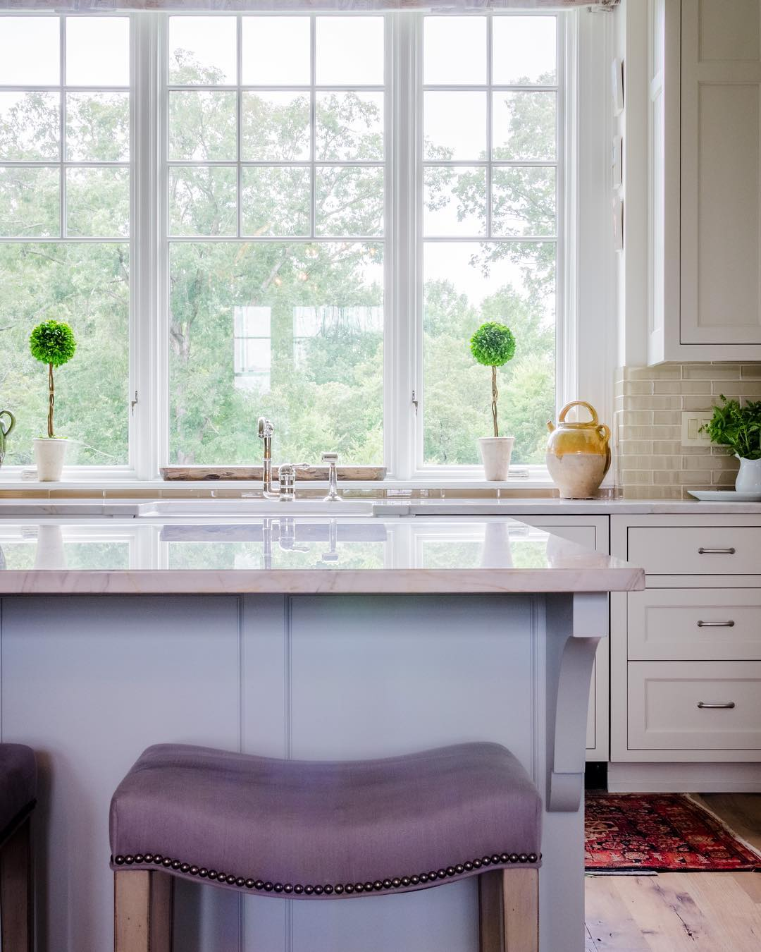 casement window with traditional grille pattern over sink in white on white kitchen