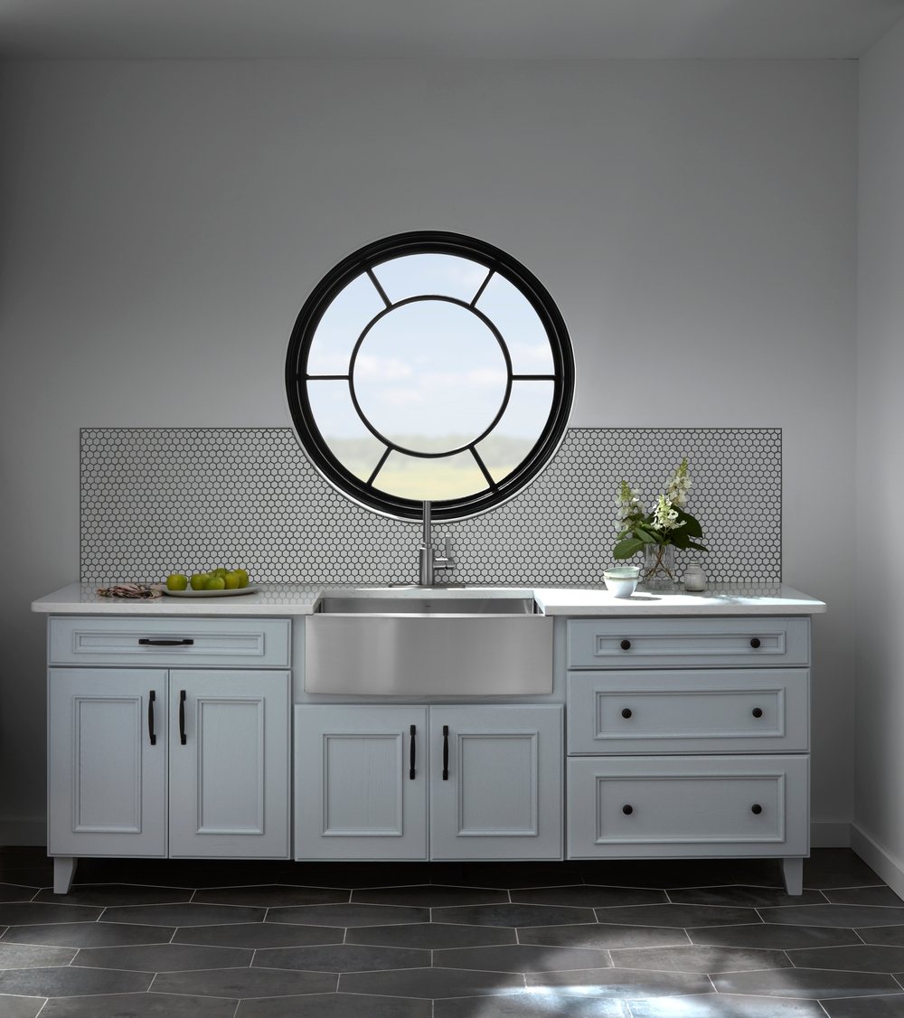 white kitchen counter and sink with black circle window with custom sunburst grilles overhead