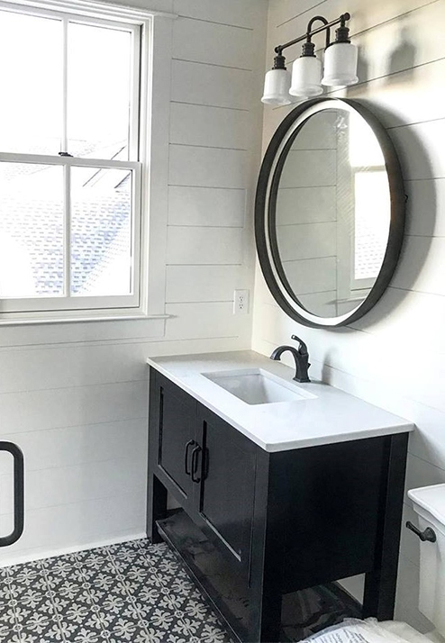 black and white bathroom features white double-hung window and black vanity with black circle mirror above