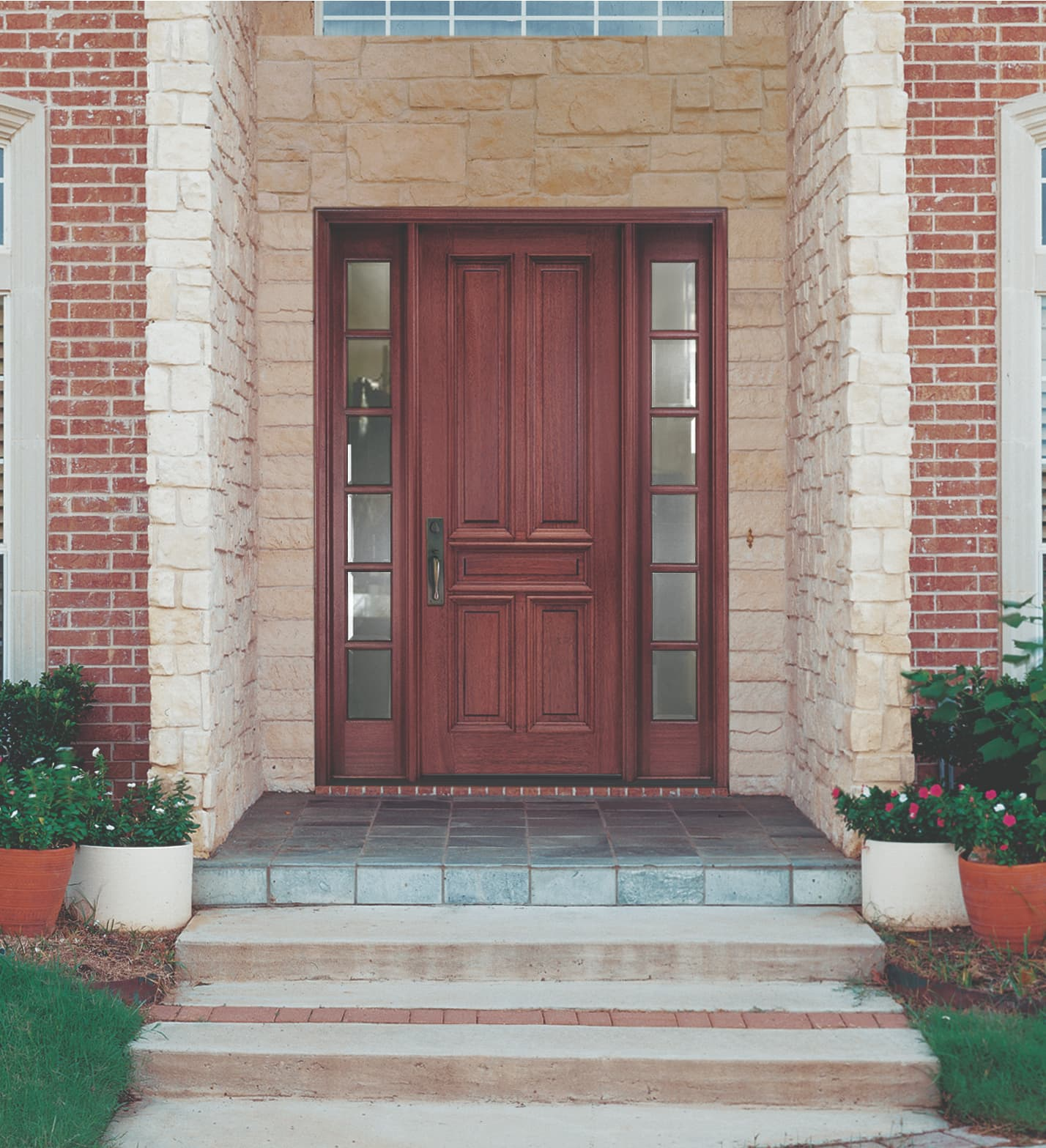 Solid wood door with glass sidelights surrounded by stone entryway