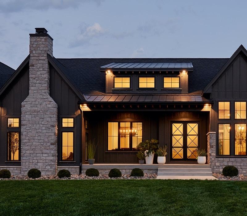home exterior at dusk stone chimney impervia fiberglass windows