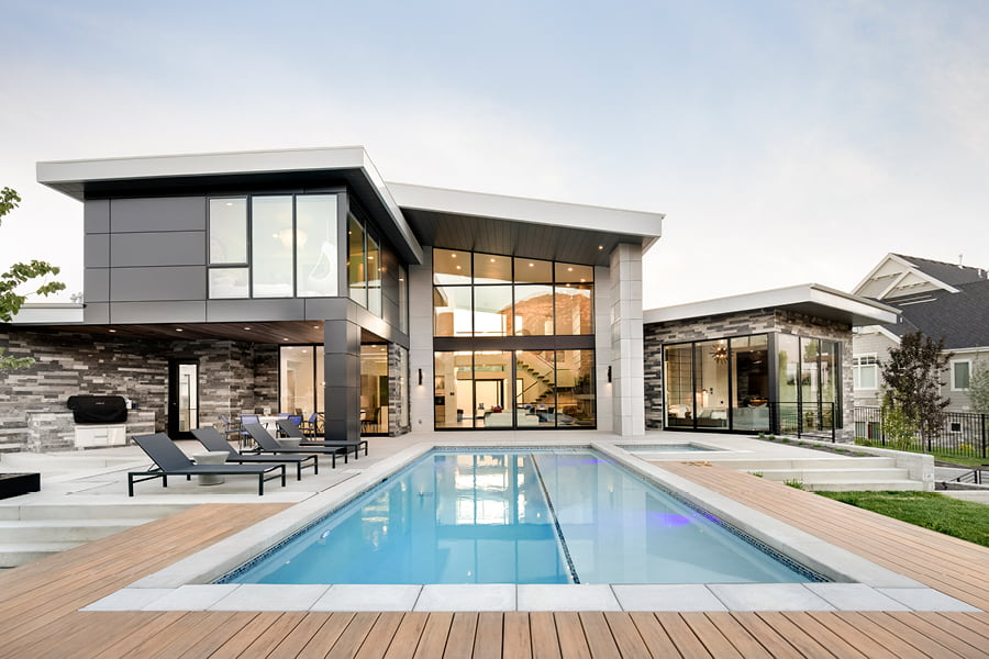 Contemporary gray home with high windows and pool in deck