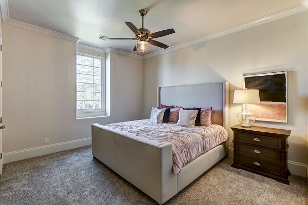 Neutral colored bedroom lit by white casement window with traditional grille pattern