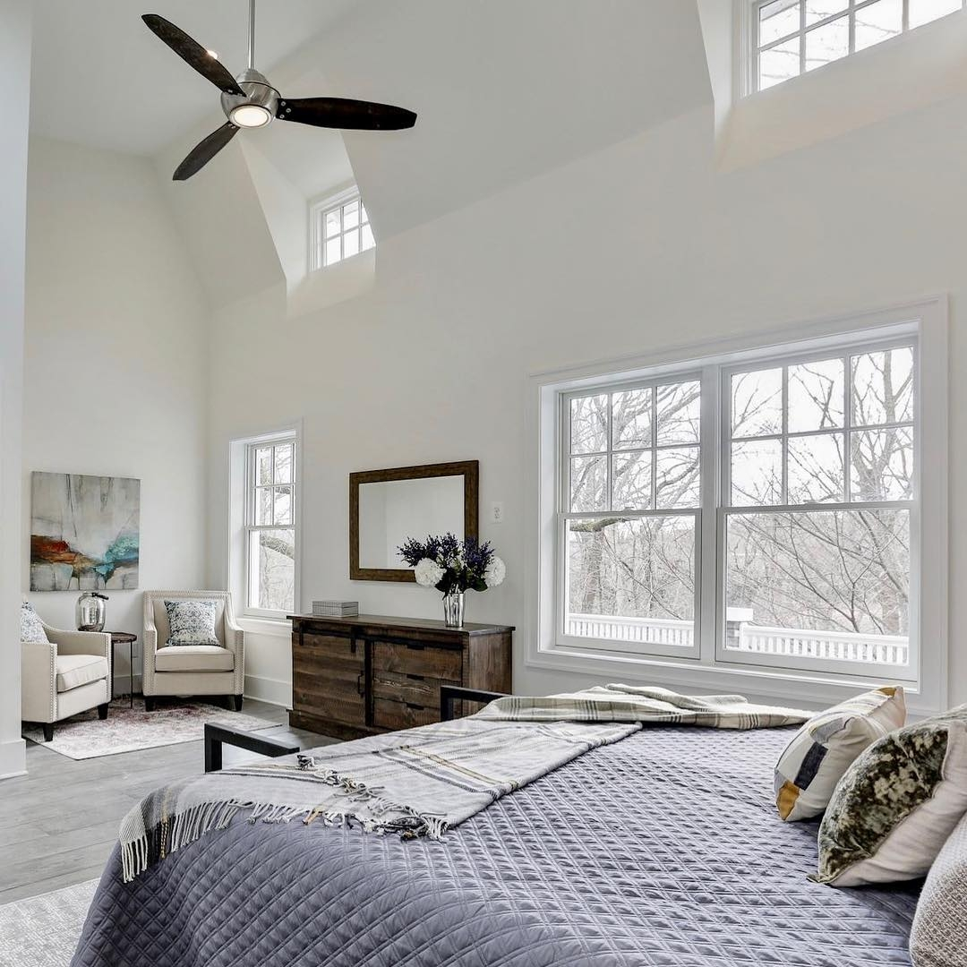 White bedroom with windows placed high near the ceiling to let in lots of light