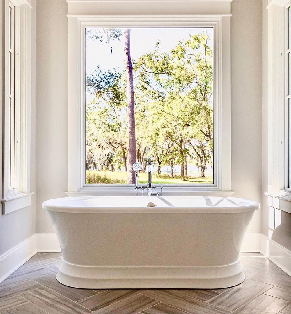 White bathroom window directly behind bathtub creates bright, picturesque space.