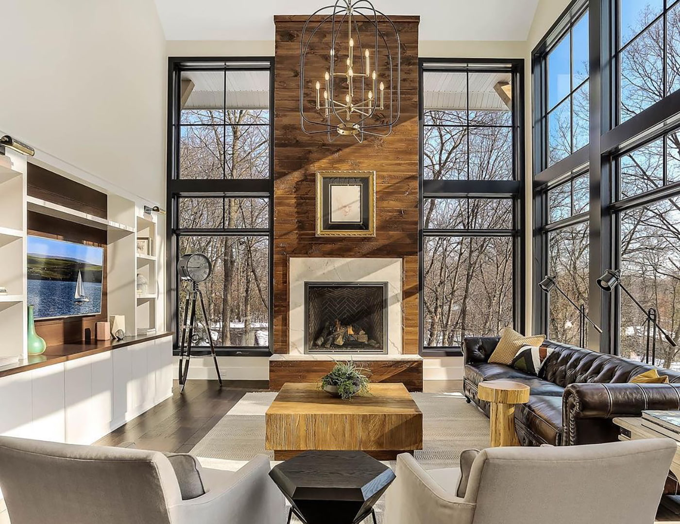 A living room with a high ceiling has floor to ceiling windows and a tall wood fireplace, topped with a grandiose chandelier.