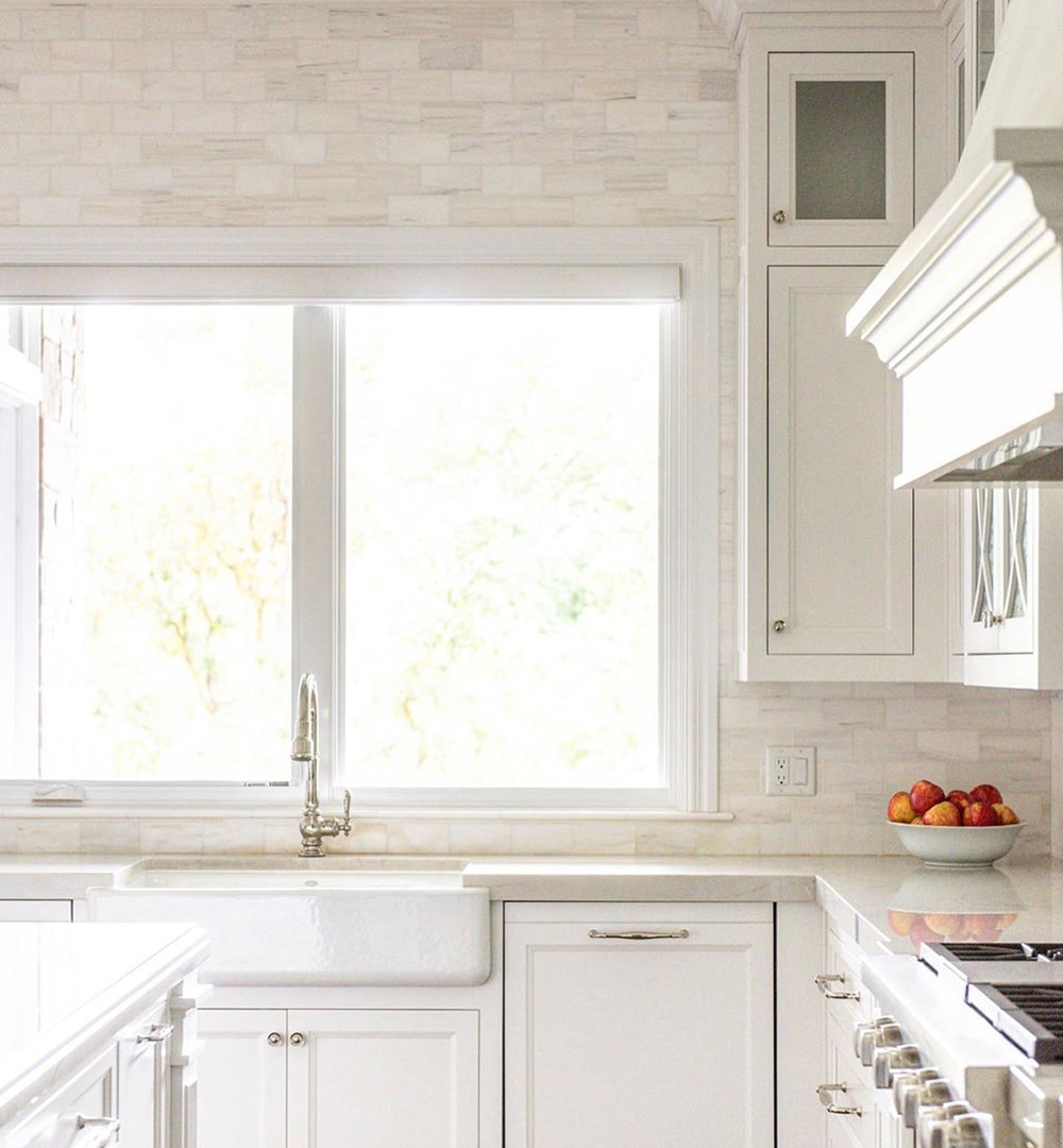 A traditional kitchen with white cabinets and backsplash features casement windows above the sink.