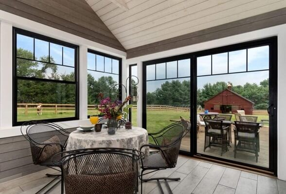 Black sliding patio door and double-hung windows in a farmhouse style sunroom