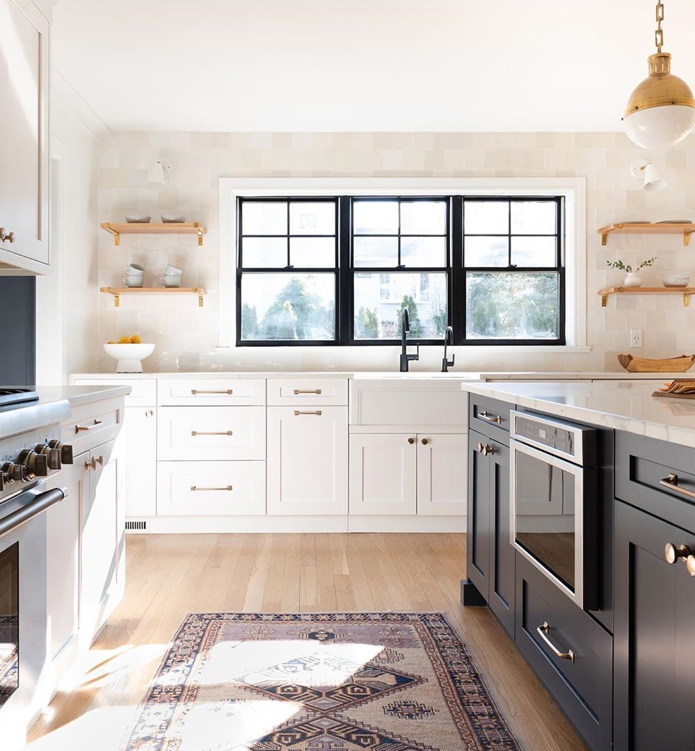 In a bright and spacious kitchen, three black single-hung windows sit side-by-side over the sink.