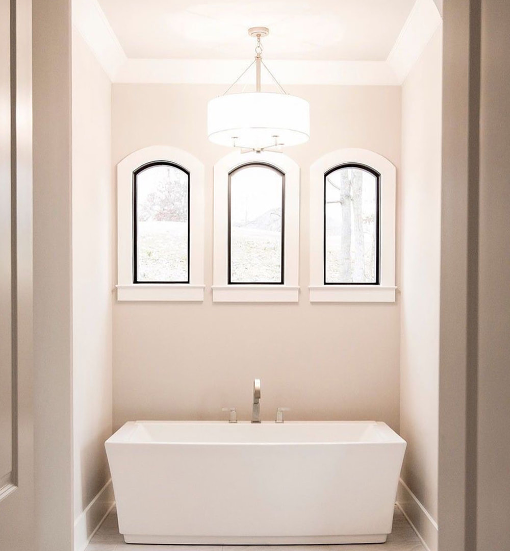 Black picture windows with white trim placed above rectangular white tub in bathroom nook.
