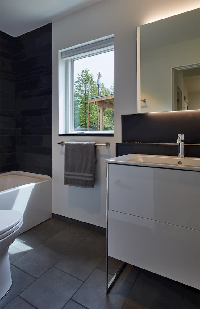 Modern bathroom with dark floor and shower wall and white window and vanity