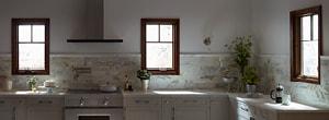 three dark casement windows taupe kitchen gray counters