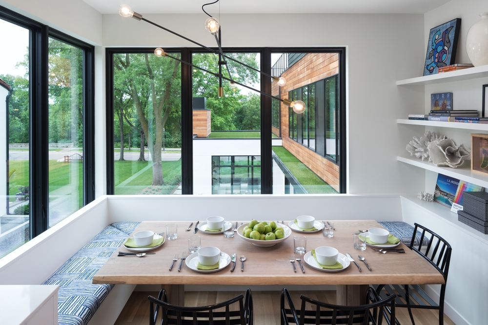 White dining room nook with benches around the table and tall black casement windows
