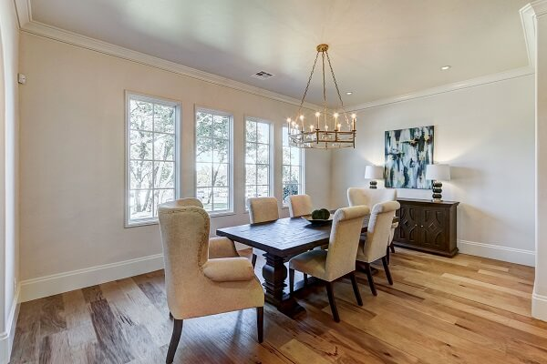 Traditional style dining room with wood floors and a row of white casement windows