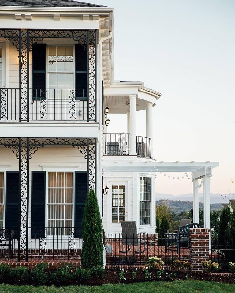 Traditional style two story white house with white double-hung windows and black shutters