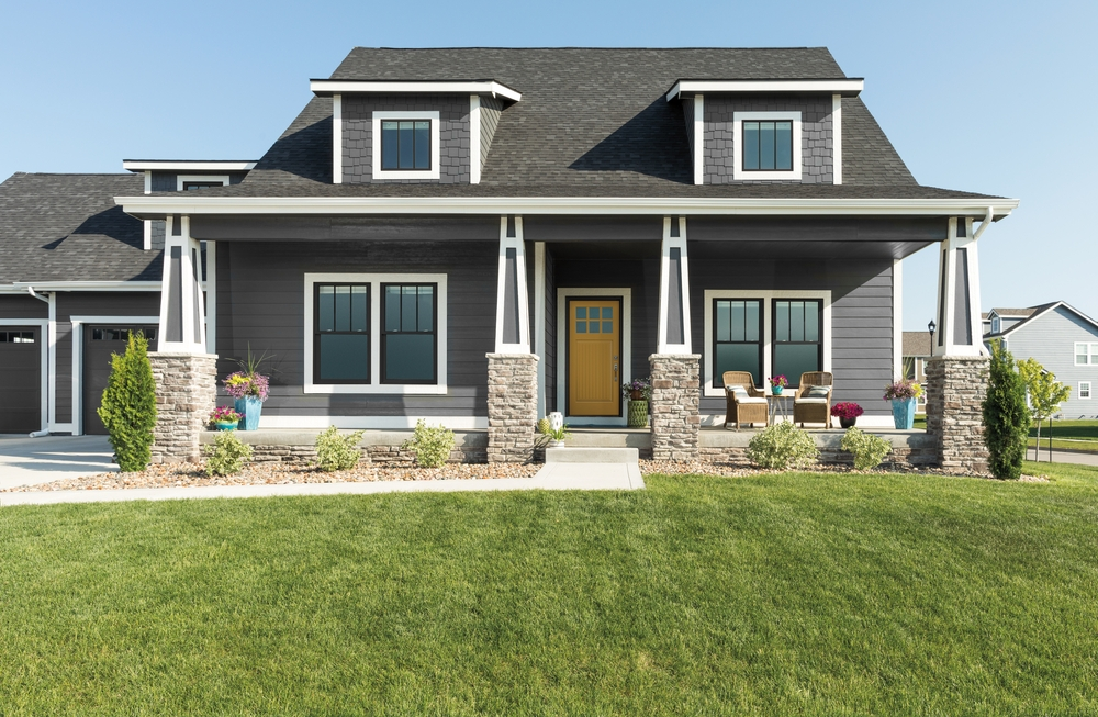 Gray cape cod style home with black windows, white trim, and a yellow front door