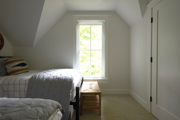 Bedroom with two twin beds and a tall casement window with cross grille pattern
