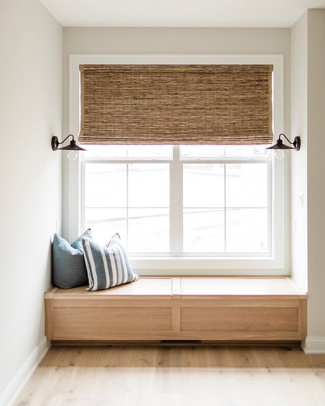 window seat with wood bench, white window, and shade