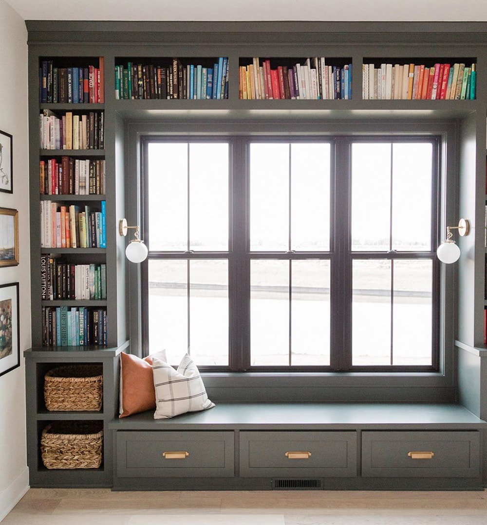 At the center of gray built-in bookshelves and a window seat are three double-hung windows with simple grilles.