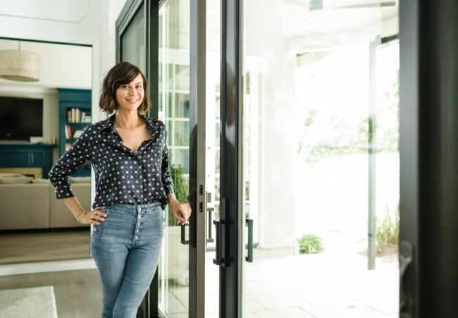 Actress Catherine Bell in her updated home standing next to sliding patio door.