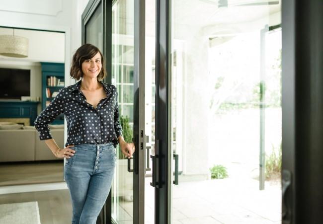 Actress Catherine Bell in her updated home standing next to sliding patio door.