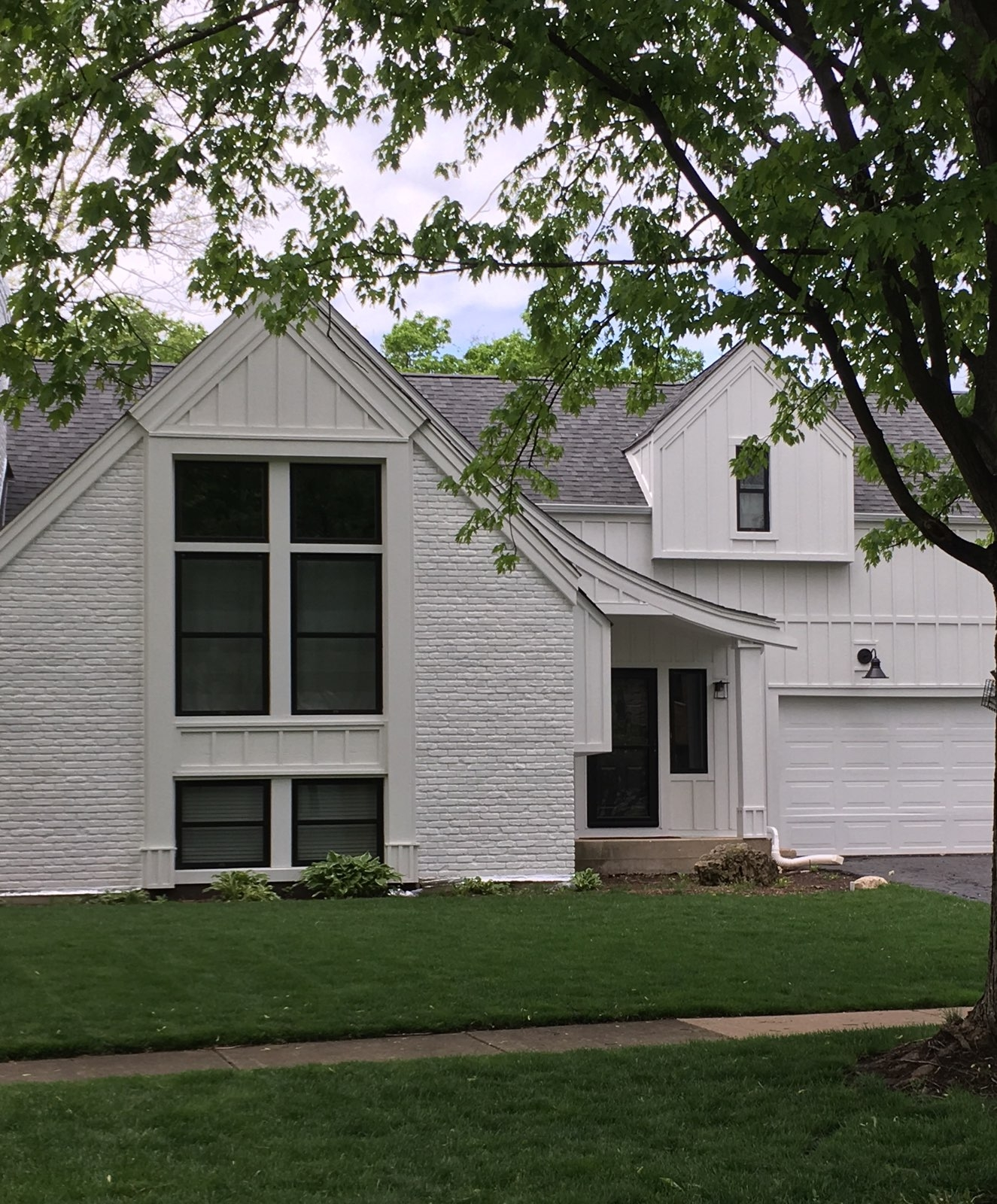 two story home with painted white brick has large black double-hung windows