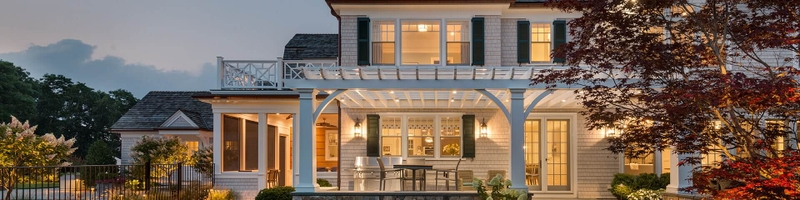 large two-story white home exterior view at dusk with porch lights on