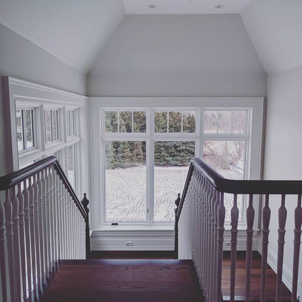 looking down at the top of the stairs to the landing with white casement windows bringing in light
