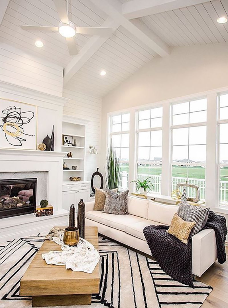 A living room has four columns of white wood double-hung windows with picture windows stacked on top.