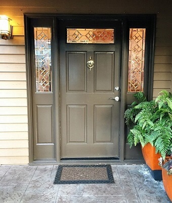 Brown and weathered front door with sidelights and a transom