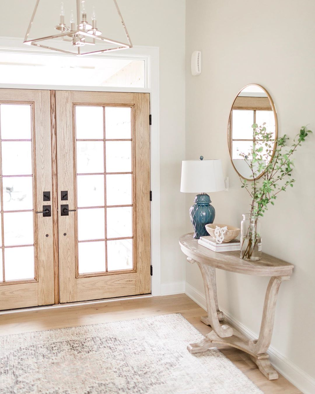 entryway with oak french patio doors and console table with blue lamp, round mirror, and greenery