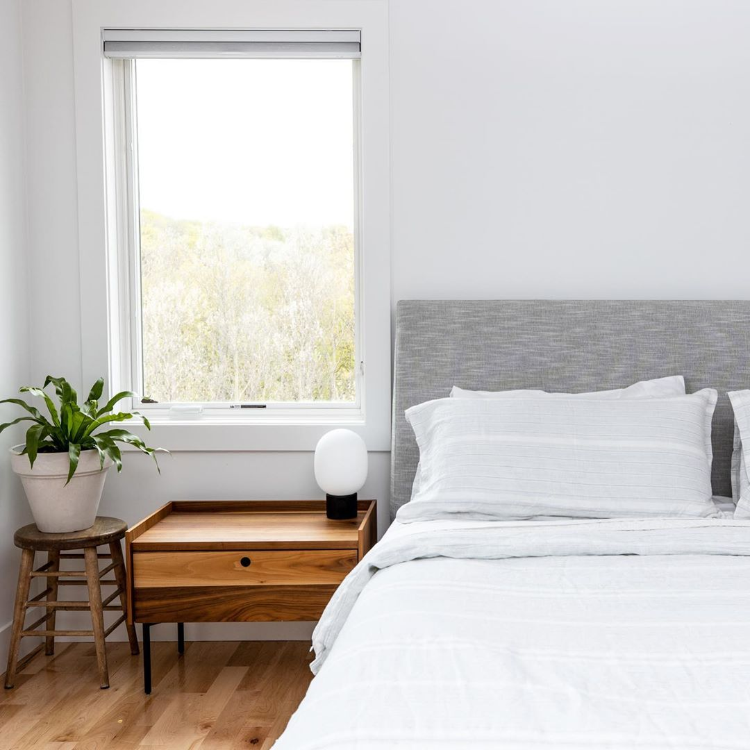 light and bright minimalist style bedroom with large casement window, nightstand, and plant