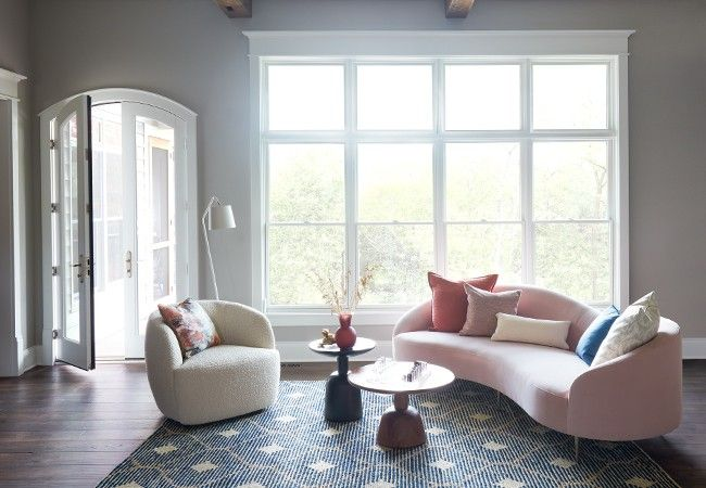 White single-hung windows with white french doors in a living room with curved furniture