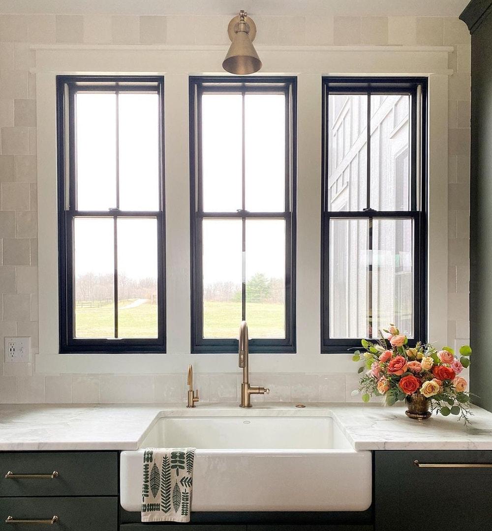 Three black kitchen windows sit above a white apron-style sink.