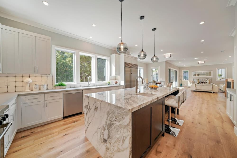 Three white casement windows placed above the sink bring light into open concept kitchen
