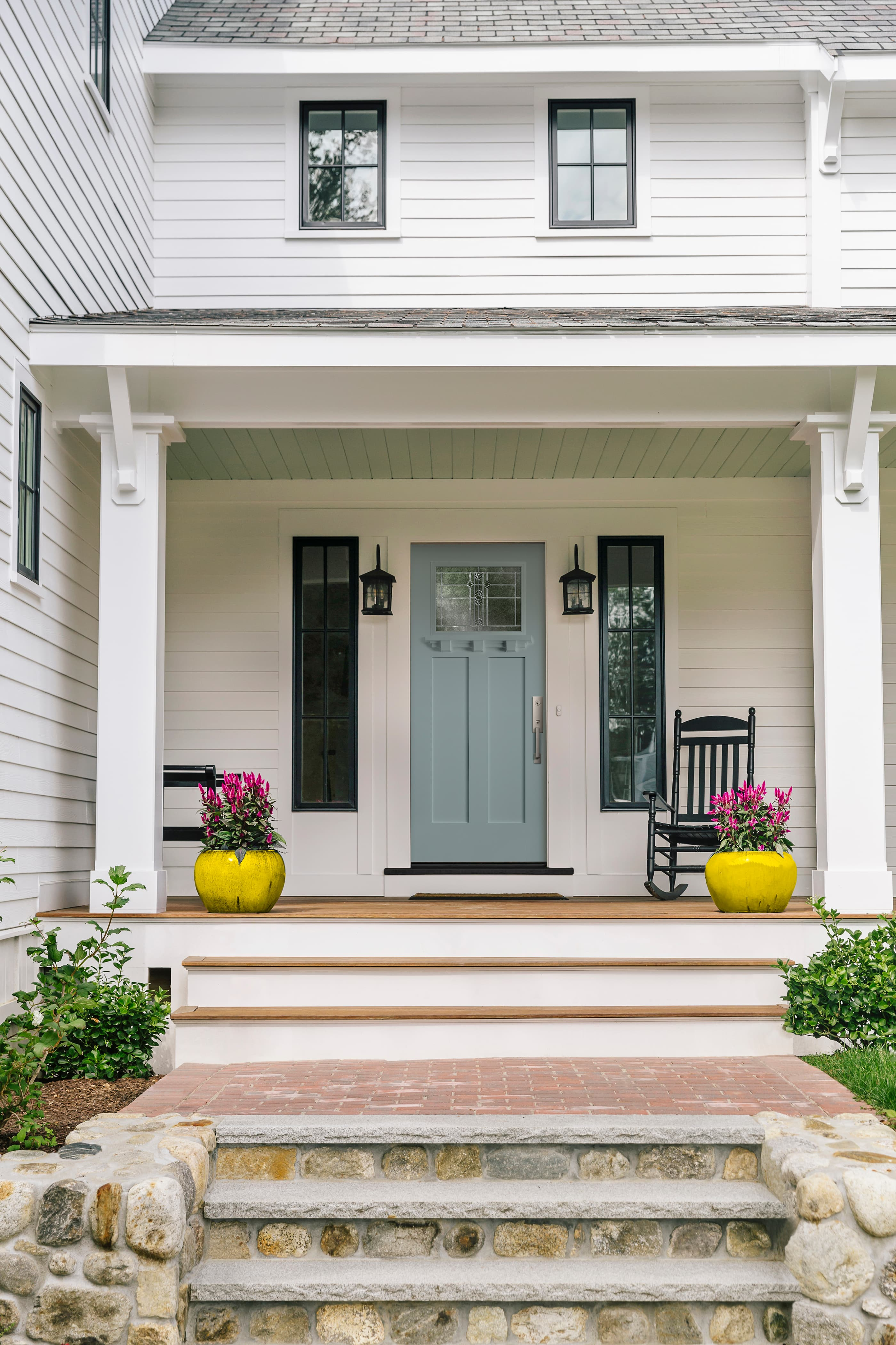 Blue craftsman front door with decorative glass and modern hardware surrounded by black windows on white house