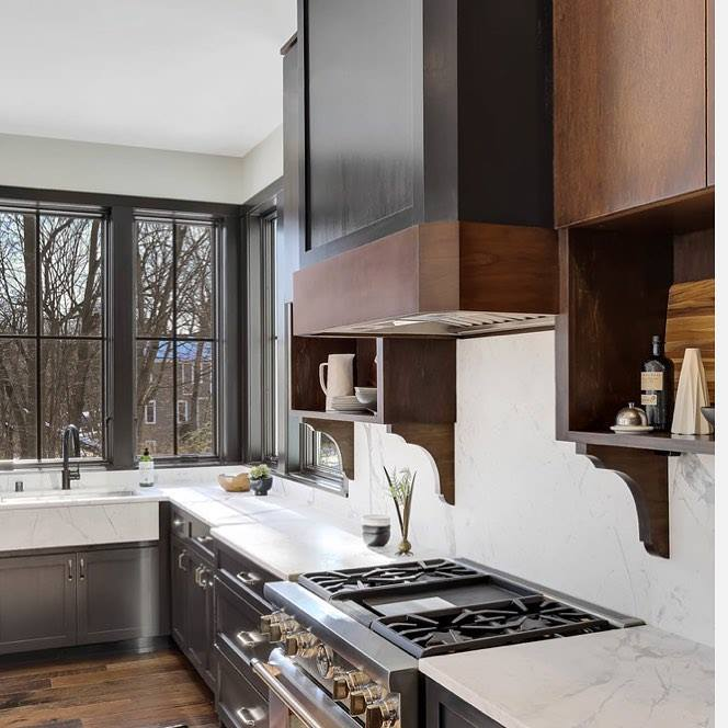 white kitchen walls are contrasted by black windows over the sink and wood cabinets over the stove