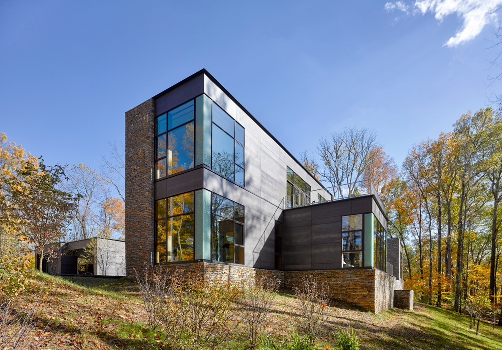Modern rectangular house with walls of glass made up of large picture windows