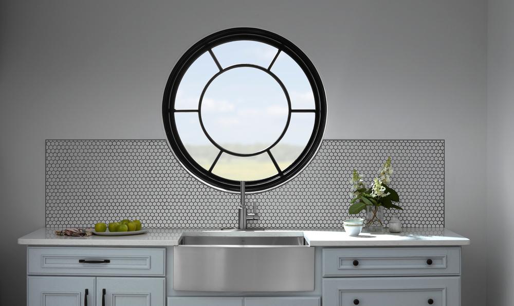 Black round window with decorative glass over farmhouse style kitchen sink