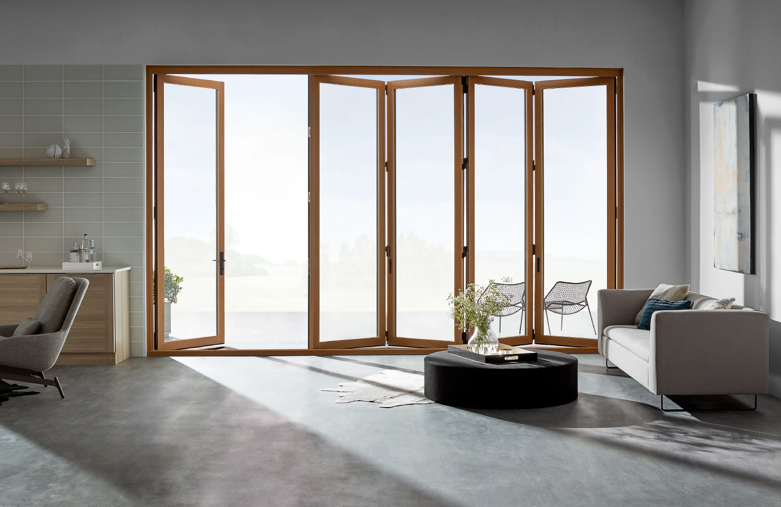 living room with light wood stained bifold patio doors partly open