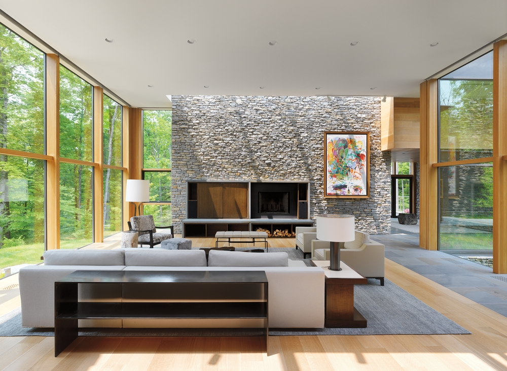 Modern living room with stone wall in the front surrounded by walls fixed wood windows on either side