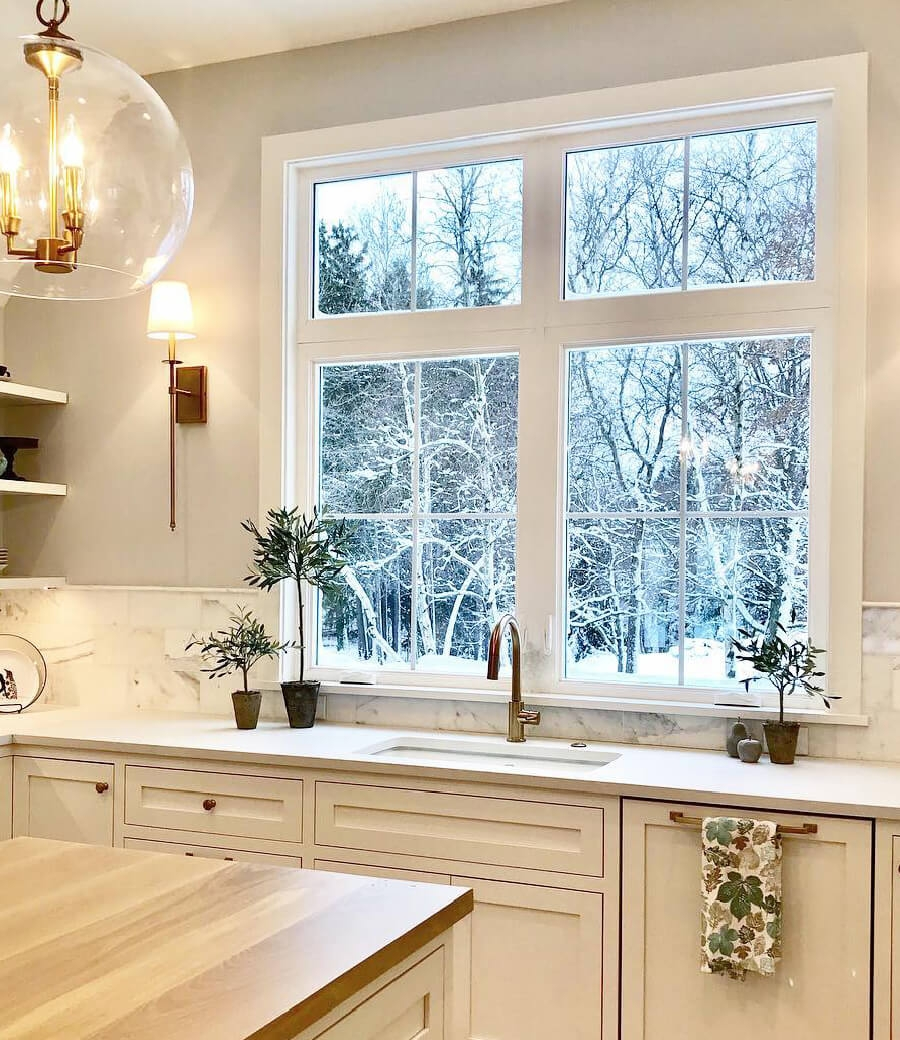 Bright white kitchen illuminated by two casement windows over the sink