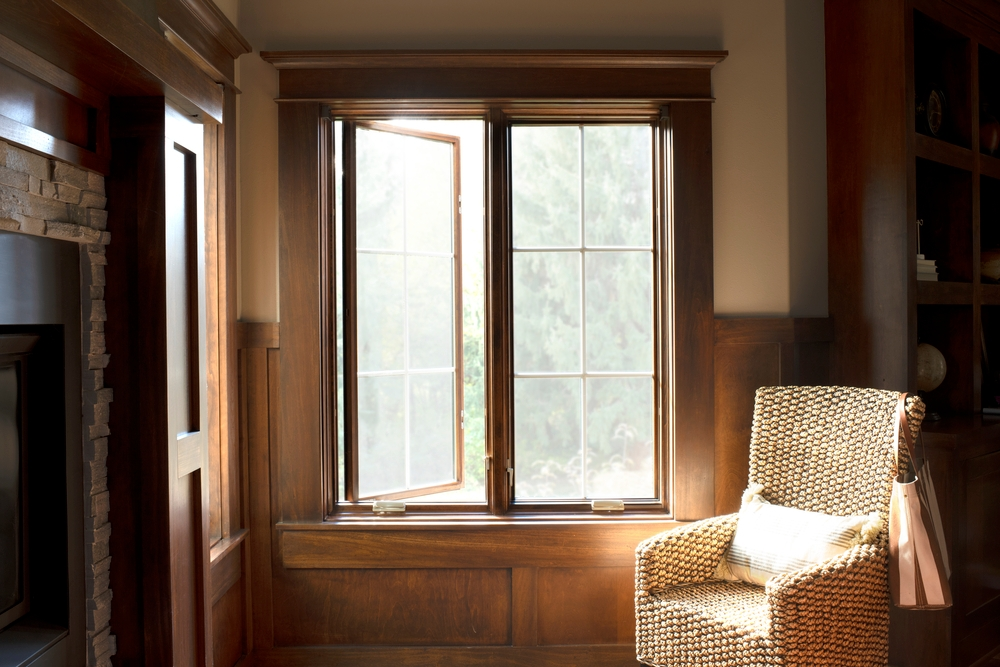 Wood paneled home office with two wide stained casement windows one opened and one closed