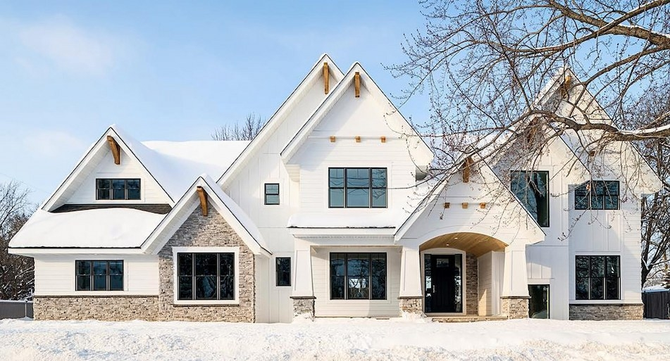 A large white farmhouse features black double-hung windows, wood corbles and warm-toned stonework
