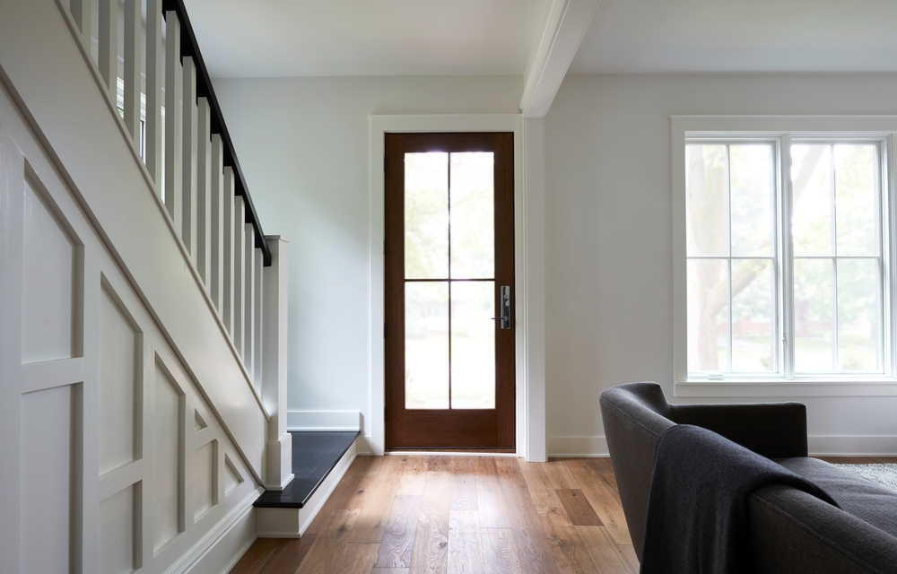 white farmhouse style entryway with stairs leading to stained wood glass front door